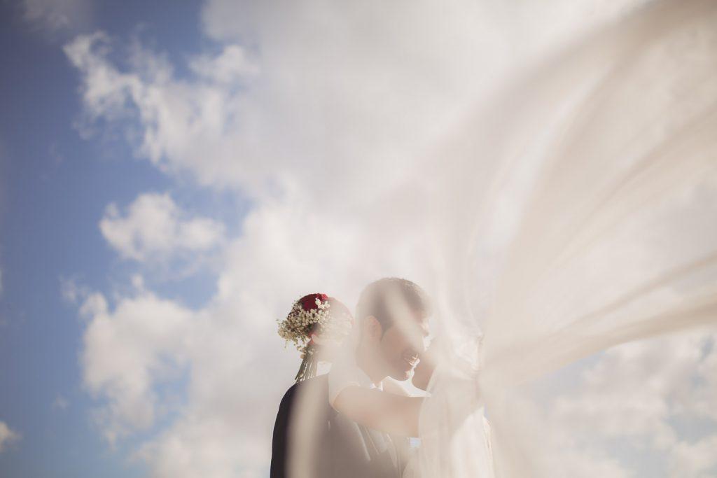 Foto de novios con el velo al viento