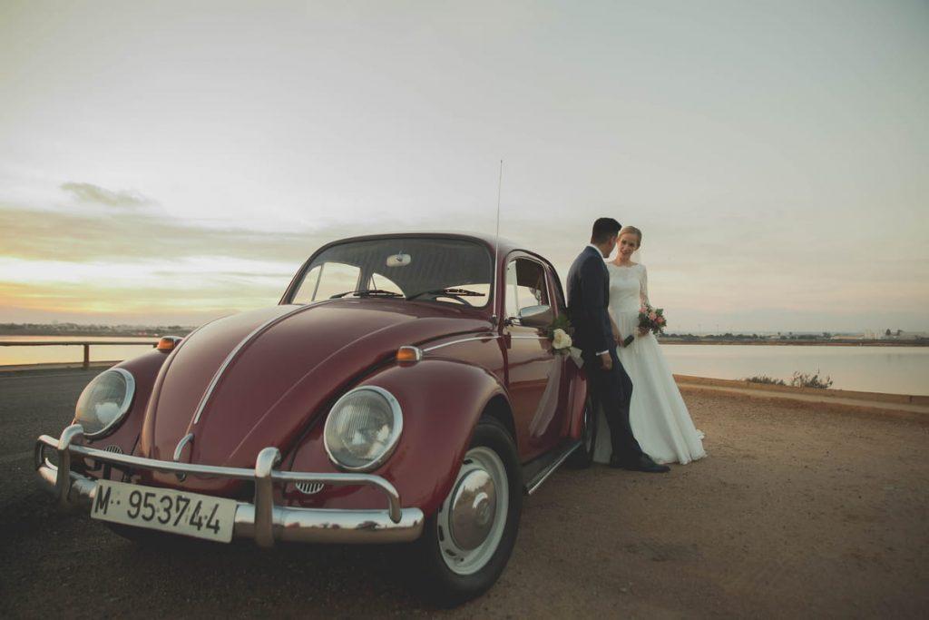 Novios al atardecer con VW Beetle