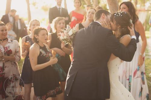 Foto de los novios besándose a la salida de la boda