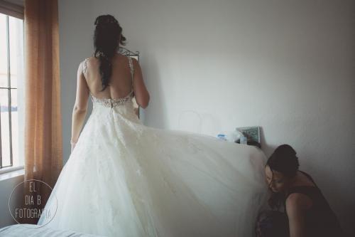 Foto de la hermana ayudando a la novia con el vestido de