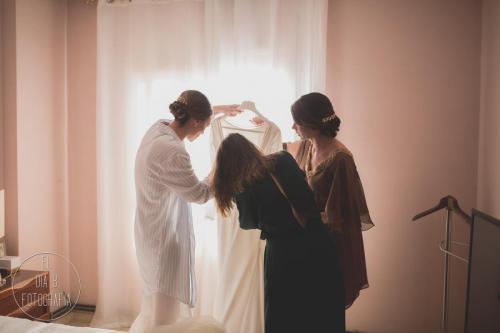 Foto de la novia y sus amigas comprobando el vestido