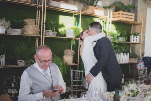 Foto de los novios besándose con ganas mientras el padre mira el móvil