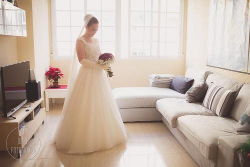 Foto de la novia viendo su ramo de rosas rojas