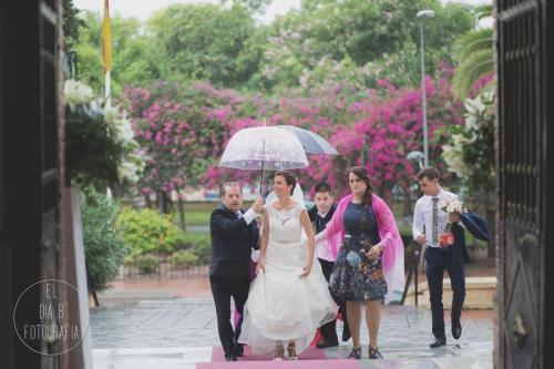 Foto de la novia llegando a la iglesia bajo el paraguas